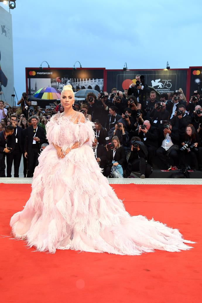 Lady Gaga donned a large feathered Valentino gown at *A Star Is Born's* Venice premiere.