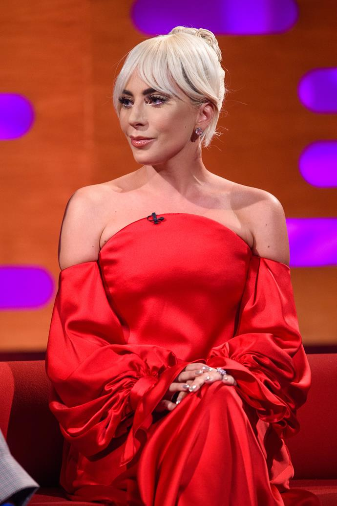 Wearing a red silk, off-the-shoulder, Gaga stuns in Carolina Herrera for her appearance on *The Graham Norton Show*.