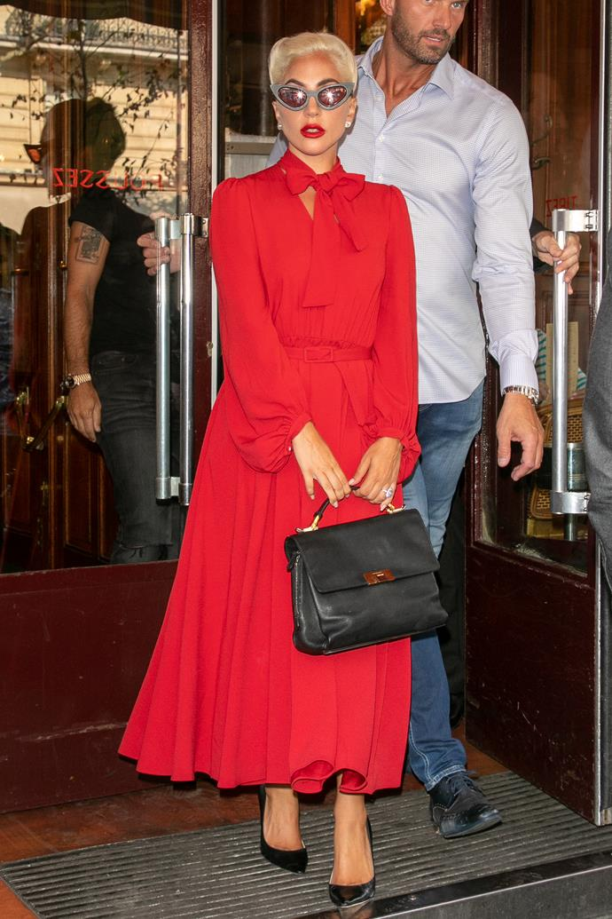A surprisingly soft look for the singer, she wore a bright red CO dress complete with cinching belt and pussy-bow neckline, with a matching lip and Balenciaga tote.