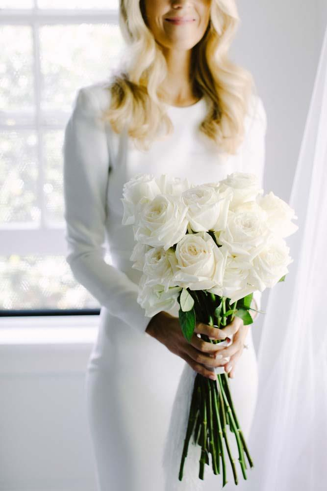 **On the flowers:** We used only white long stemmed roses in my bouquet to complement the simplicity of my dress. To my surprise, my florist added a white tassel to my bouquet which I loved—it was so fun! For the ceremony and reception we had a mix of white roses, orchids and hydrangeas set off against lots of greenery.