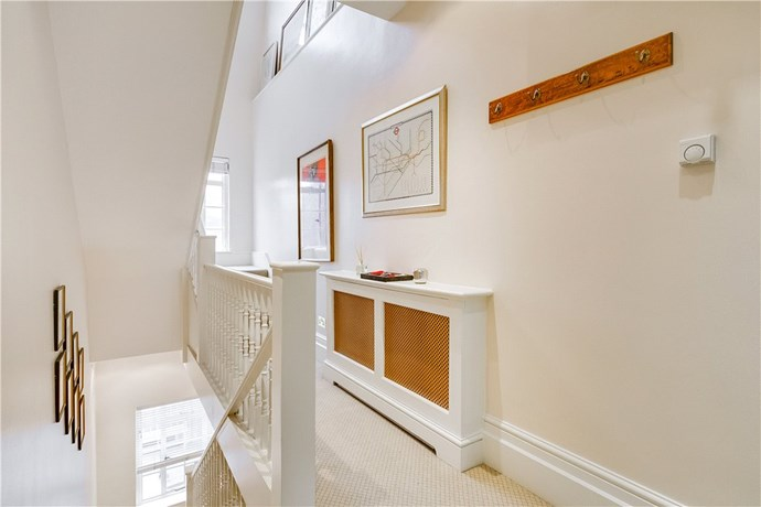 The hallway and grand staircase, which provides access to the flat's three floors. Courtesy Knight Frank