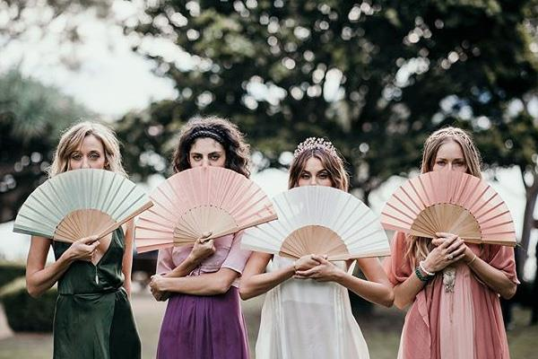 **The Bridesmaids:** <br><br> The bridesmaids wore Awaveawake's handmade, dyed silk dresses. Cut-offs from the dresses were used to make matching handheld fans.