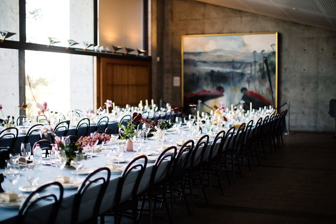 """**On the style of the reception:** I wanted to bring subtle elements from our Kyoto engagement into our wedding. I had my talented friend Stephanie Huxley design origami-inspired invitations that came in hand-folded envelopes. Aleksandra, our incredible florist also workshopped an ikebana inspired vision for our table arrangements, using bold flowers placed purposefully in hand-made ceramics. I commissioned [Claire Mounsher](https://www.instagram.com/claire_mounsher/?hl=en target=""""_blank"""" rel=""""nofollow"""") to construct a cherry blossom paper art backdrop for our photobooth. And while it wasn't exactly Murcutt's vision, we thought the minimalistic design of the Bundanon Trust building was also reminiscent, with lots of concrete, enormous sliding doors and a soaring slanted roof."""