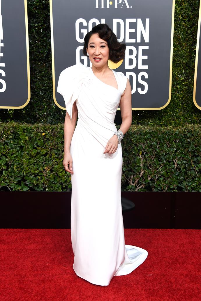"**Sandra Oh in Atelier Versace**<br><br> ""A perfectly elegant gown that doesn't steal attention from her megawatt smile. The asymmetry and ruching are a touch of Old Hollywood for an actor at the peak of her powers."" *Tom Lazarus, copy director.*<br><br> ""Points for having the best accessory of all, Andy Samberg."" *Chris Xi, beauty and features assistant.*"
