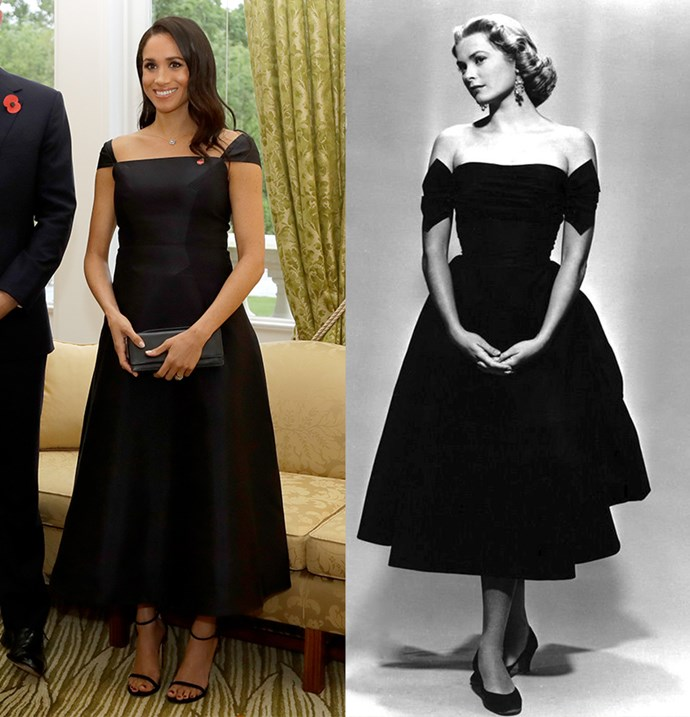 In a full-skirted black midi dress with off-the-shoulder sleeves.