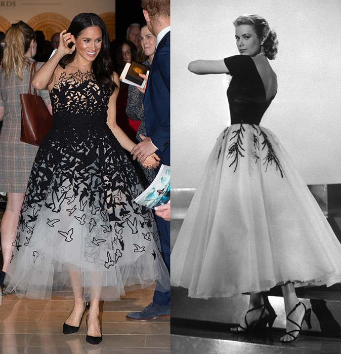 In a black and white organza gown with a tea-length hem.