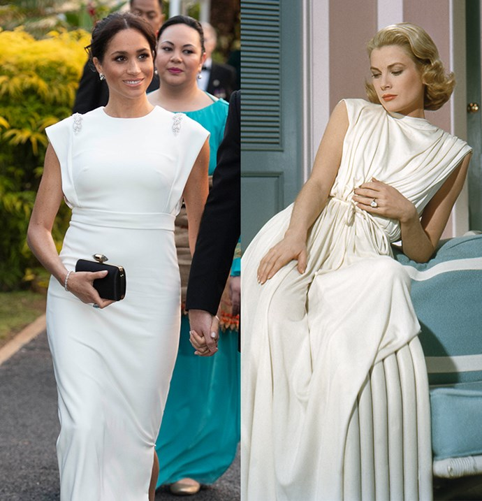In a white gown with a high neck and cinched waist.