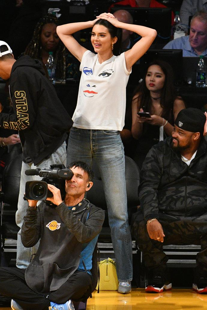 In a white print tee and silver boots to watch the Los Angeles Lakers and the Houston Rockets play on October 20th, 2018.