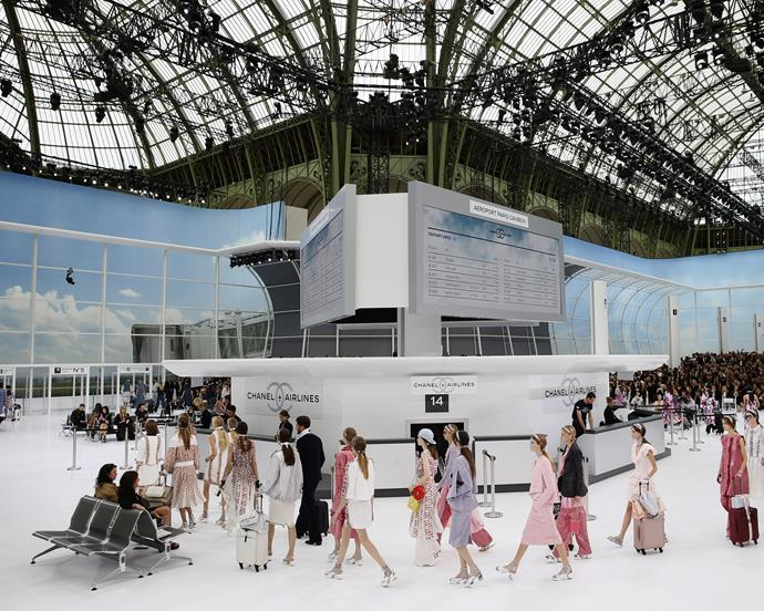 ***Chanel spring/summer '16*** <br><br> Lagerfeld continued his love for travel at spring/summer '16, where he transformed the Grand Palais into a literal airport (the home of '*Chanel Airlines*', of course). With models toting Chanel suitcases on the runway, the show was an exercise in travel chicness.