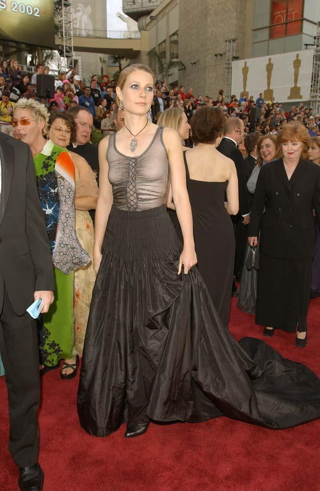 """***Gwyneth Paltrow in Alexander McQueen, 2002***<br><br> After appearing in 1999 in her princess-perfect pink Ralph Lauren, Paltrow went the opposite way and wore this moody McQueen gown, which didn't go down well with critics. """"There were a few issues; I still love the dress itself but I should have worn a bra and I should have just had simple beachy hair and less makeup,"""" Paltrow said of the look in 2013. """"Then, it would have worked as I wanted it to—a little bit of punk at the Oscars."""""""