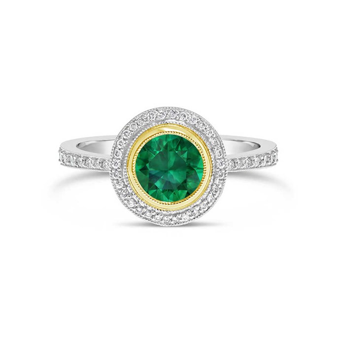 """**The Vibe: A Hint Of Gold** <br><br> Round-cut emerald and diamond halo ring set in a fine yellow gold bezel setting, POA at [Fairfax & Roberts](https://www.fairfaxandroberts.com.au/product/emerald-diamond-halo-engagement-ring/