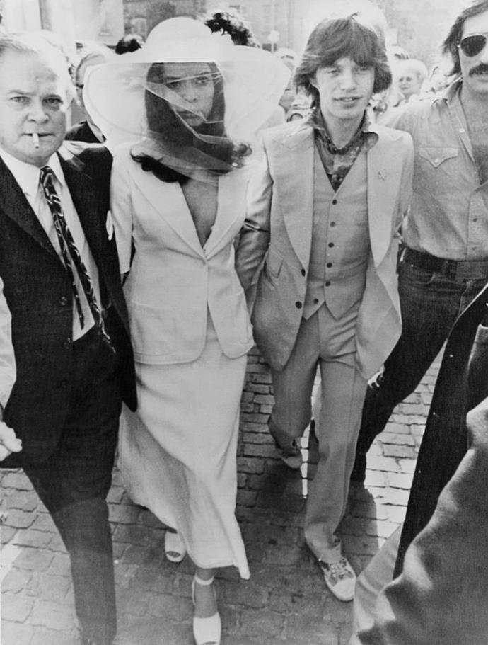 **Bianca Jagger** <br><br> At her 1971 wedding to Mick Jagger in Saint-Tropez, Bianca wore an outfit that was controversial at the time, but later become her most famous. Instead of a conventional dress, the Nicaraguan beauty paired a flowy skirt with a white Yves Saint Laurent blazer, and wore a rose-adorned sunhat and veil. <br><br> *Image: Getty*