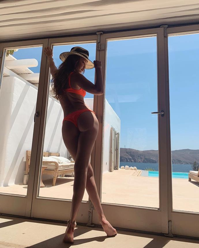"When kicking off the vacation, Gigi posted an image of herself in their villa wearing a bright orange bikini by New York City-based designer [Danielle Guizio](https://www.danielleguiziony.com/swim|target=""_blank""