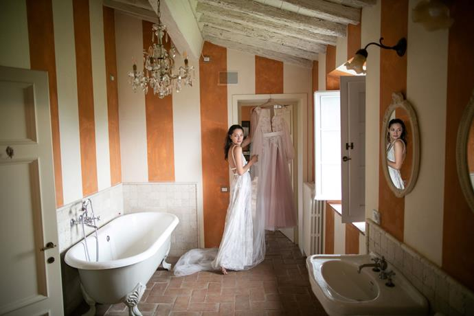 **On her arrival and exit from the ceremony:** We got ready at the villa where the wedding celebrations took place. It was very interesting that the master bedroom where I was getting her hair and make up done was right above the room where Samuel was getting ready and it had a Juliet balcony overlooking the aisle and the tree/altar where I would later walk down to get married. After the ceremony, we walked back to the cocktail hour area where our guests surprised us by showering us with rose petals.