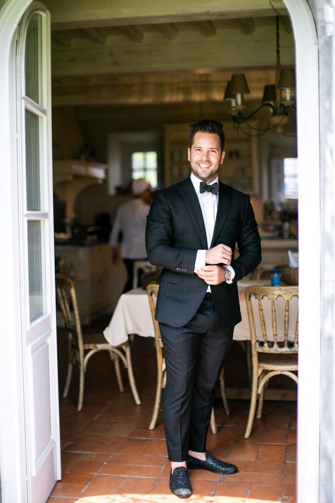 "**On the groom's look:** Samuel wanted a classic, timeless black tie look. He wore a custom bespoke black suit by Colorado Springs based Bespoke Evan Delaney, a crisp white dress shirt with french cuffs and a black bow tie. He wore black ""Thame"" Jimmy Choo Slippers to complete the look."