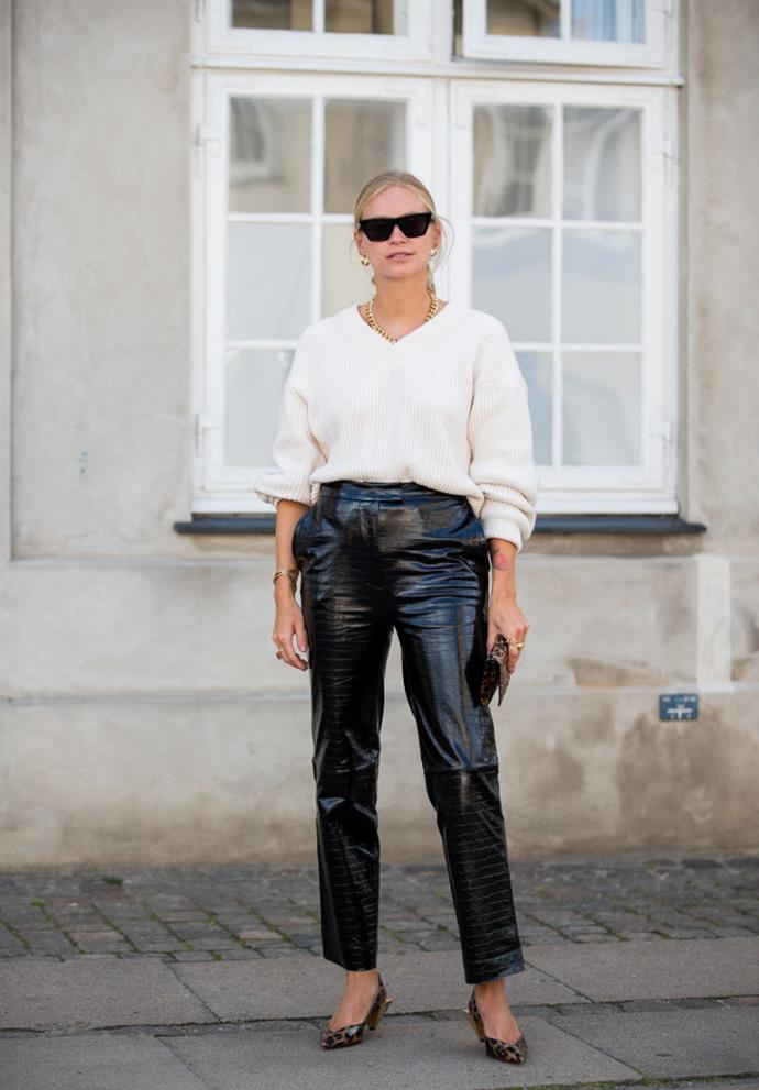Blogger Tine Andrea wears a slouchy white sweater and leather trousers.