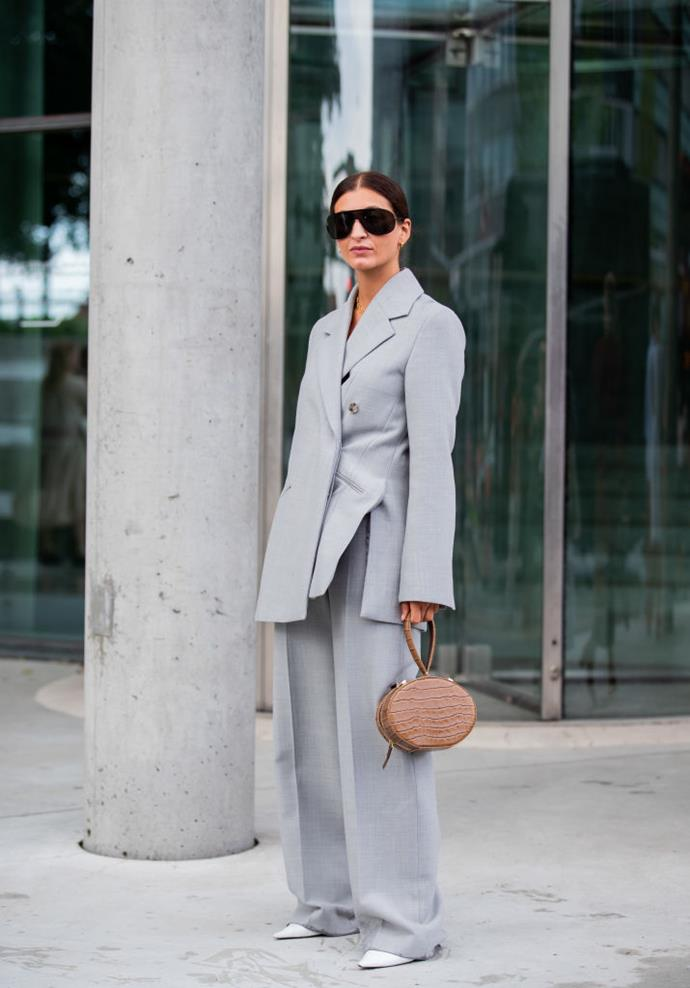 Katarina Petrovic wears an asymmetrical grey suit and oversized sunglasses.