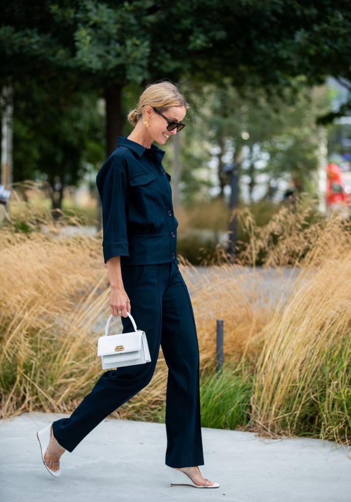 Cecilie Thorsmark wears a dark navy suit, wedge sandals, and a Balenciaga handbag.