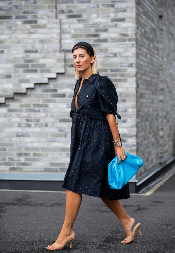 Aylin Koenig wears a dotted shirt dress, Prada headband, and Bottega Veneta slouchy clutch.
