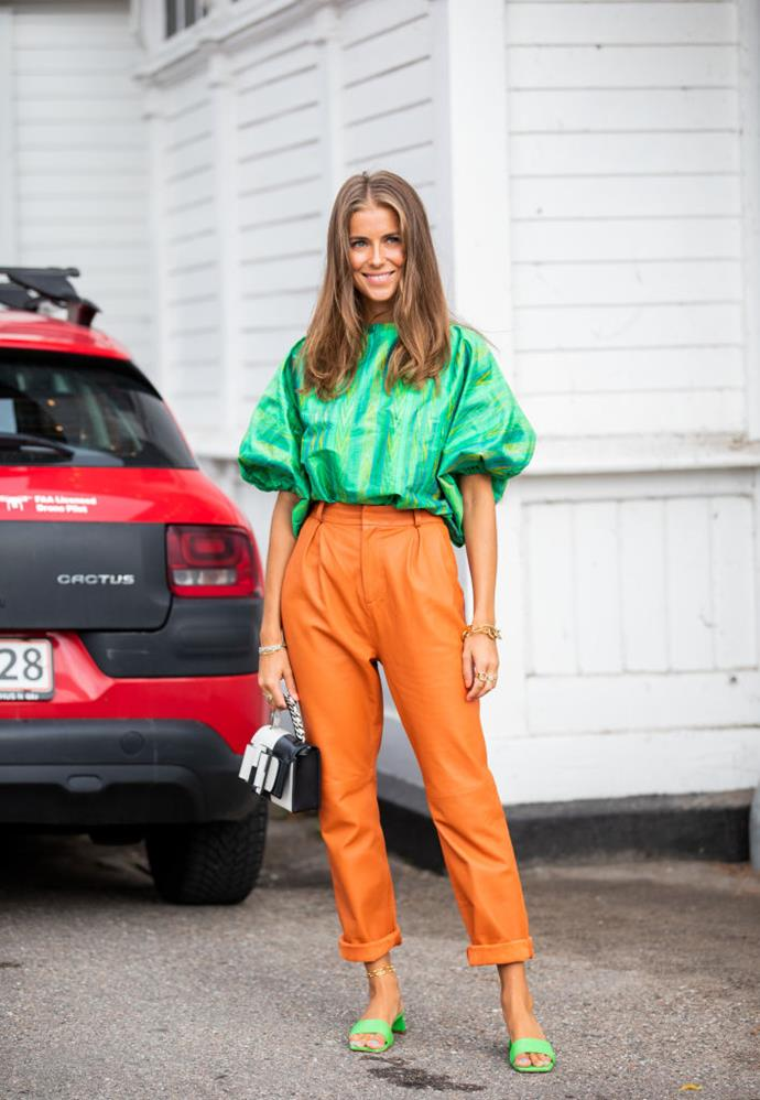 Nina Sandbech wears a green frilled top and orange leather trousers.