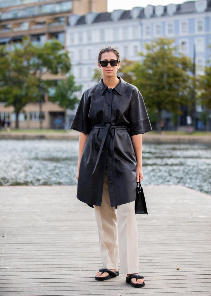 Elisa Schenke wears an oversized leather coat and padded flip-flop sandals.