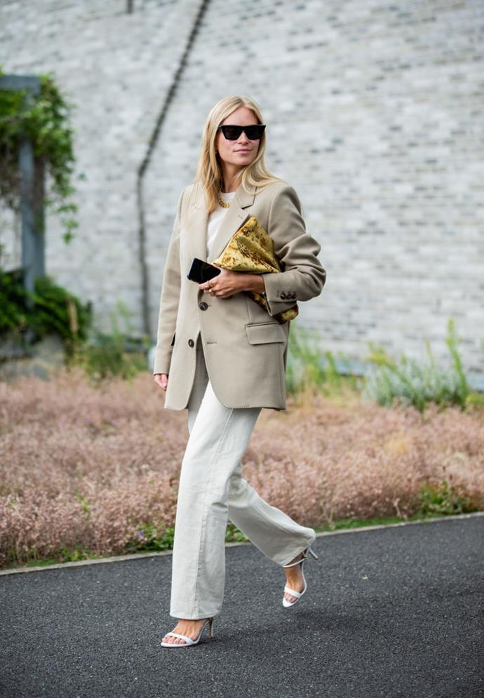 Blogger Tine Andrea wears a khaki blazer and dusty white trousers.