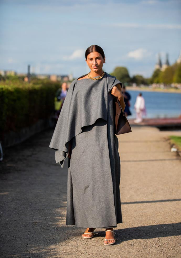 Katarina Petrovic wears a draped grey dress and The Row strappy sandals.
