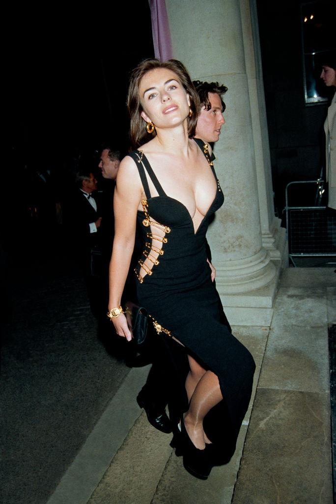 **Elizabeth Hurley (1994)** <br><br> Hurley was a relatively unknown figure when she attended the *Four Weddings And A Funeral* premiere with her then-boyfriend, Hugh Grant, in this iconic safety-pin dress by Gianni Versace. <br><br> The dress catapulted Hurley to global stardom, and proved that a single dress can be the ultimate branding choice.