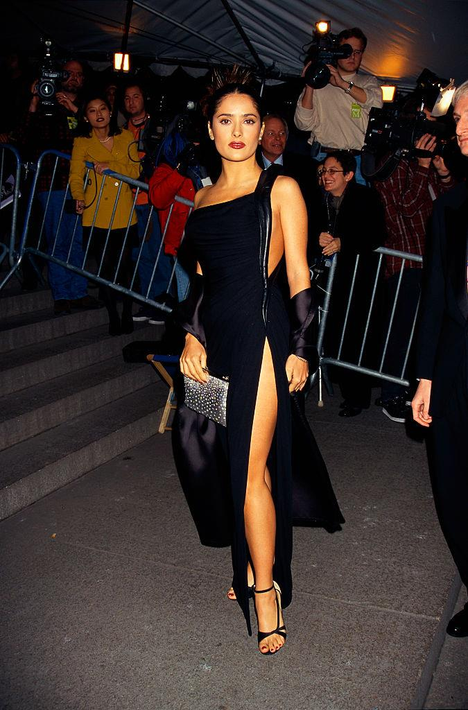 **Salma Hayek (1997)** <br><br> In red carpet history, there are a few thigh-high leg split moments that changed the game. One of the most famous was Salma Hayek's dress at the 1997 Met Gala, which left only a tiny piece of fabric between her upper and lower waist.