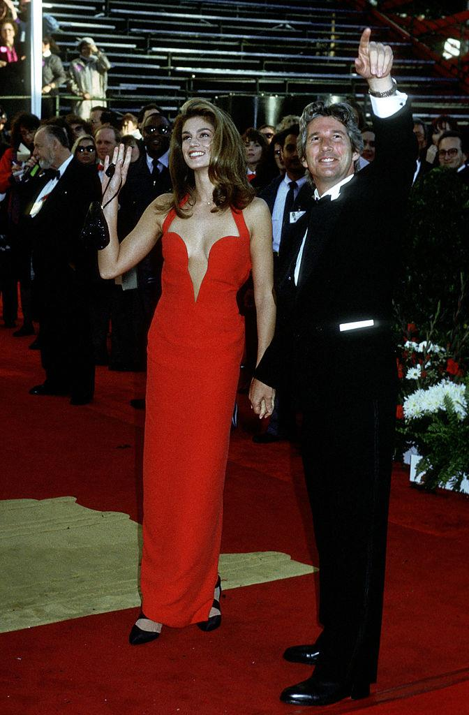 **Cindy Crawford (1991)** <br><br> Crawford, a bona-fide supermodel, wore this red Versace gown to the Academy Awards in 1991 with her then-husband, *Pretty Woman* actor Richard Gere. The dress became famous for its low cleavage cut, which was rare (and very risqué) for its time.
