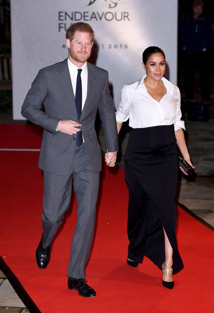 """**2. The classic formal ensemble** <br><br> While pregnant in February 2019, Meghan wore an ensemble by Givenchy, which featured an unbuttoned white shirt with a floor-length black skirt. Appearing to channel the style of [Carolyn Bessette-Kennedy](https://www.harpersbazaar.com.au/fashion/meghan-markle-carolyn-bessette-kennedy-18072