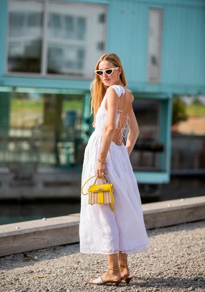 An open-back dress and a little straw bag.