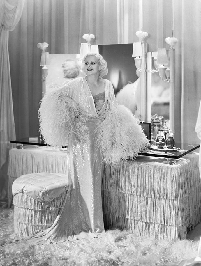Jean Harlow wearing a sequin and feather robe over a slip in *Dinner At Eight* in 1933.