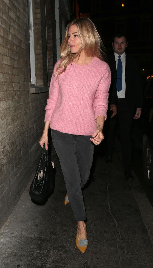In a pink knit and black skinny jeans.