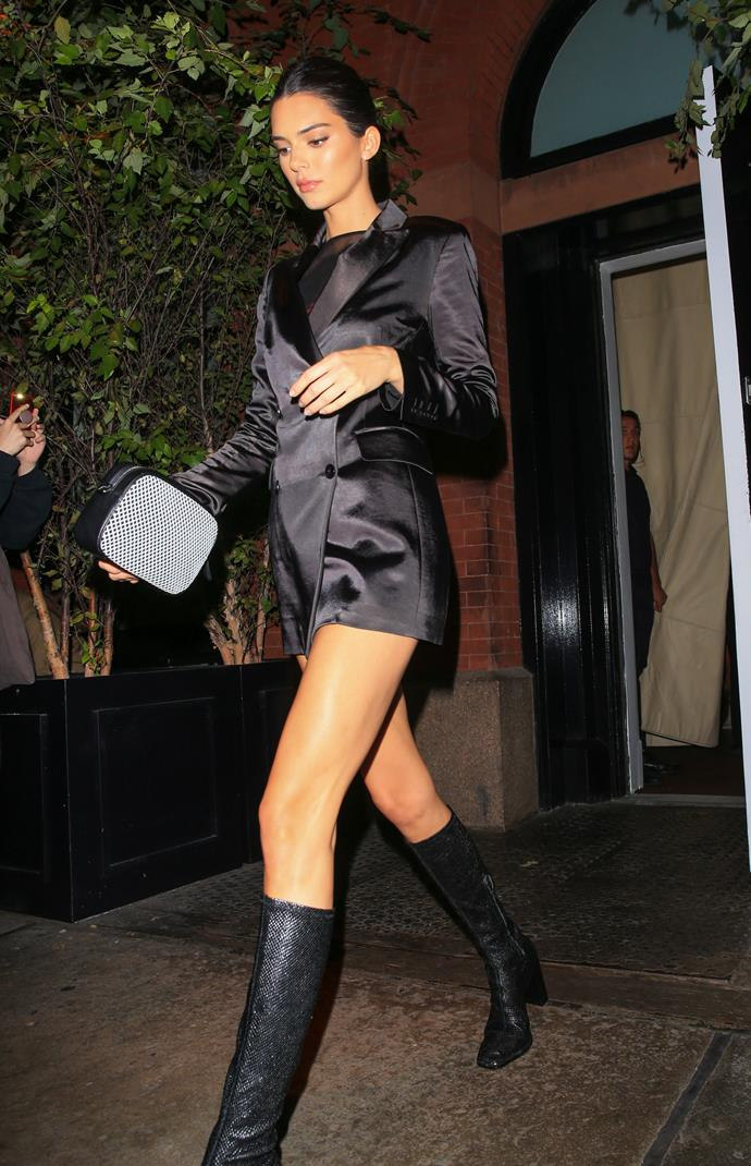 Kendall Jenner wearing a drazer and knee-high boots to DKNY's 30th anniversary party during New York Fashion Week, in September 2019.