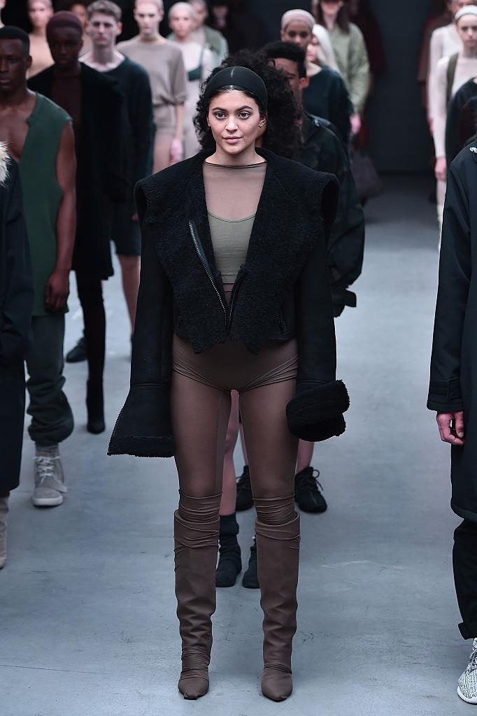 **Kylie Jenner for adidas Originals x Kanye West YEEZY SEASON 1 at New York Fashion Week Fall 2015**<br><br>  Another Kar-Jenner who's made a cameo on the runway? Beauty mogul Kylie Jenner. The younger Jenner sister appeared on the catwalk in Kanye West's YEEZY SEASON 1 collaboration with adidas Originals sporting slicked back hair and extremely minimal makeup, rendering her almost unrecognisable.