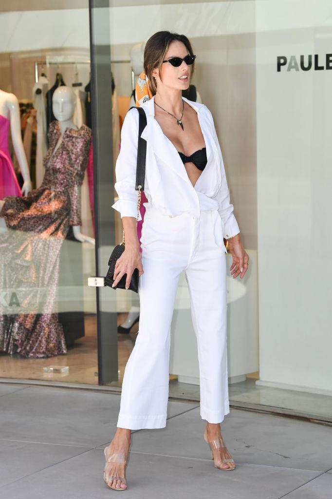 Alessandra Ambrosio contrasting a black bra with a white jumpsuit in May 2019.