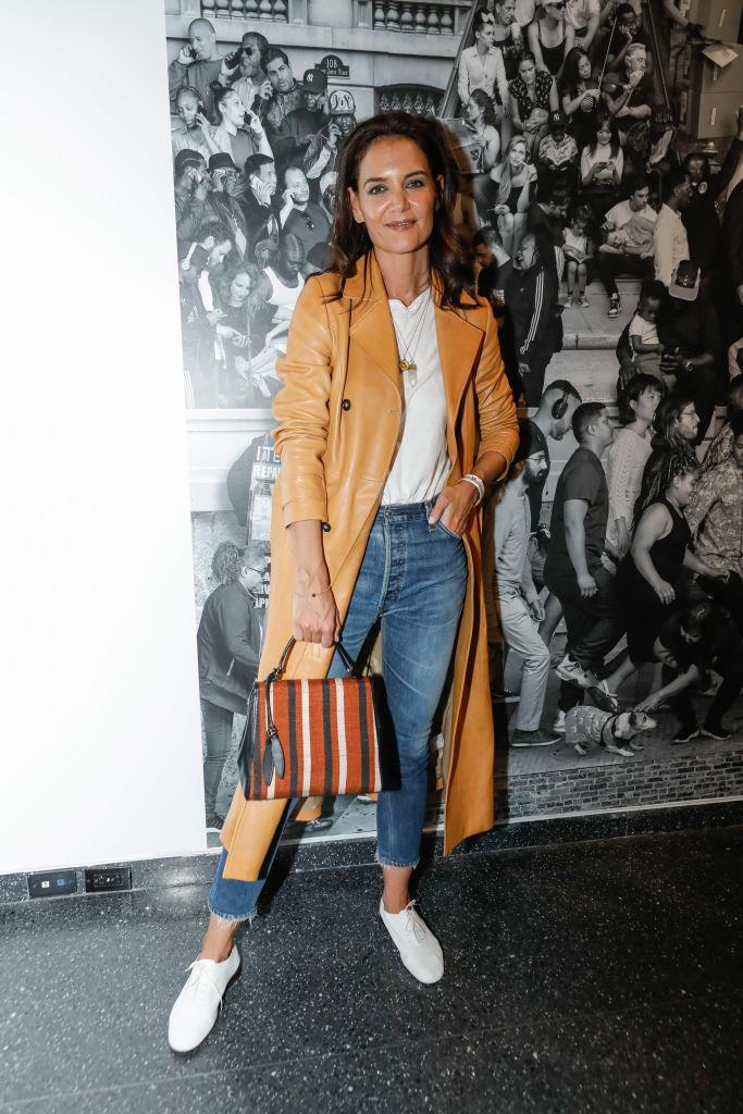 In a leather trench with blue jeans and white sneakers on October 2, 2019.