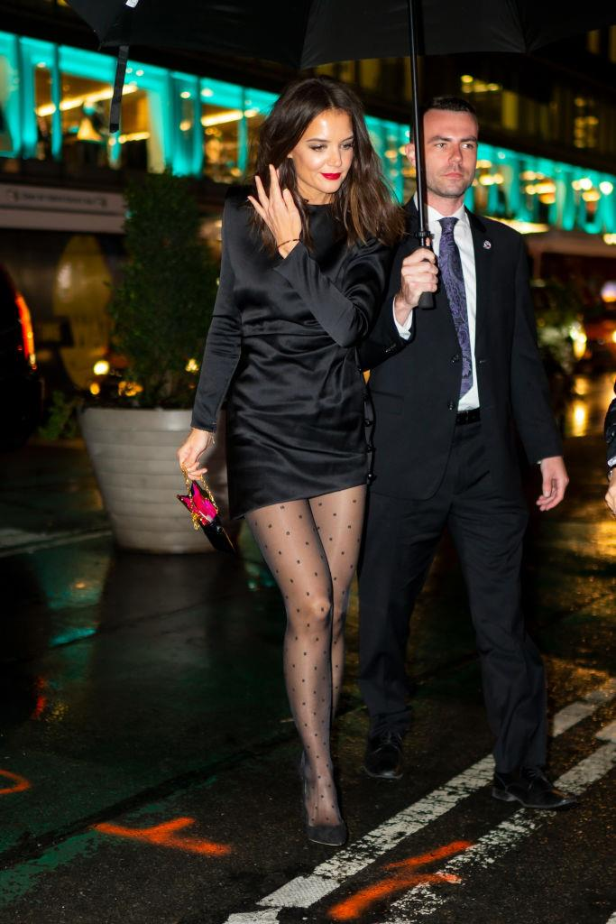 In a black satin mini dress by Saint Laurent Paris, with dotted tights, on October 22, 2019.