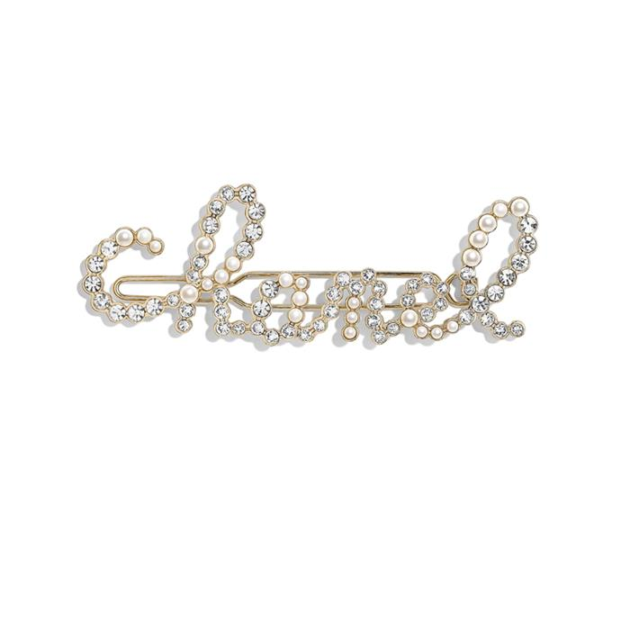"""***A Statement Barrette***<br><br> Barrette, approx. $1,156, in store at [Chanel](https://www.chanel.com/us/fashion/p/AB2850Y47927Z8905/hair-accessory-metal-glass-pearls-strass/ target=""""_blank"""" rel=""""nofollow"""")."""