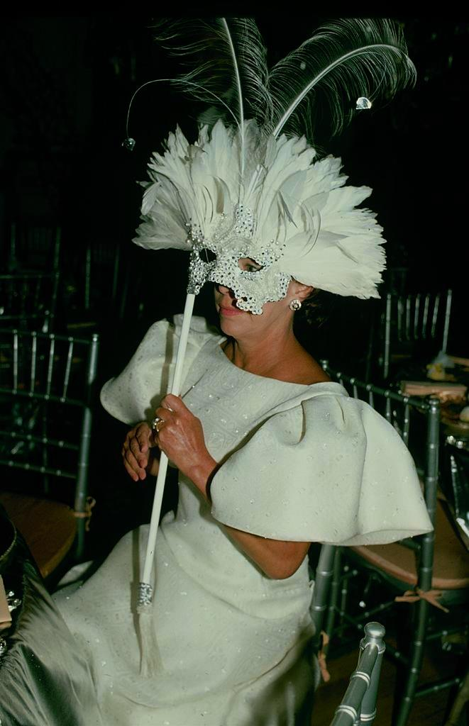 In statement sleeves and a mask for a masquerade ball in 1990.