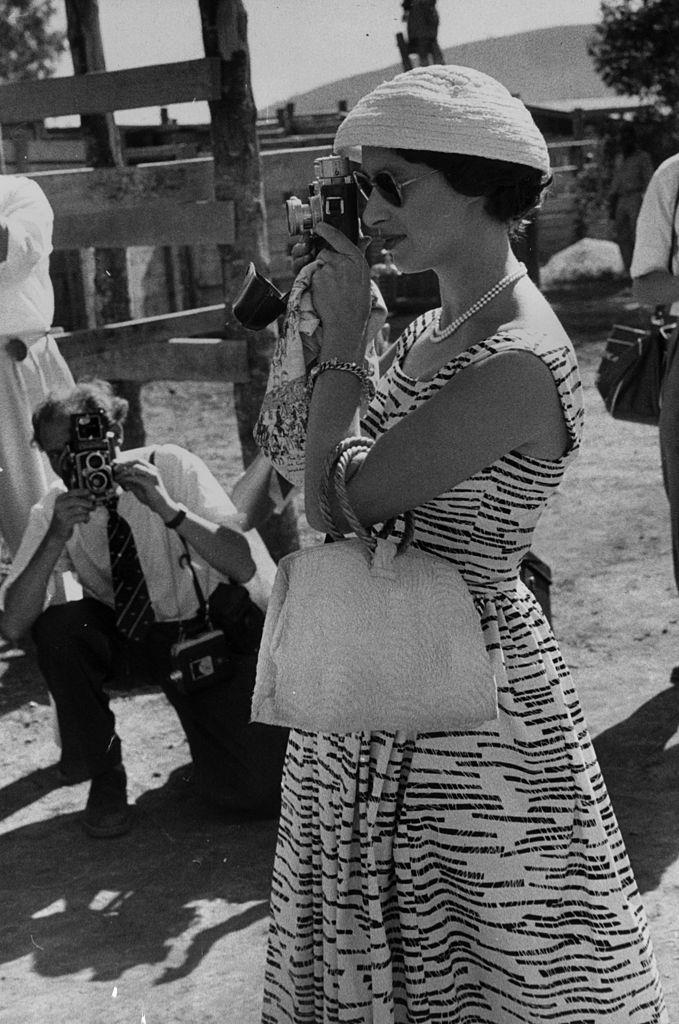 Elegant in a patterned sundress and understated millinery in Africa in 1956.