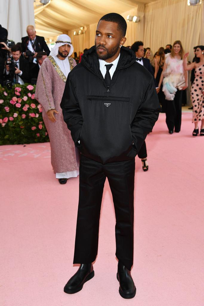 **Frank Ocean in Prada at the Met Gala (2019)** <br><br> 2019's 'Camp'-themed Met Gala saw celebrities arriving in all kinds of pompous garments—instead of Frank Ocean, however, who showed up in a relatively simple black Prada hoodie. Though it's possible he chose to ignore the theme, many argued that Ocean's unexpected look embodied the 'camp' aesthetic in its own meta, ironic way.
