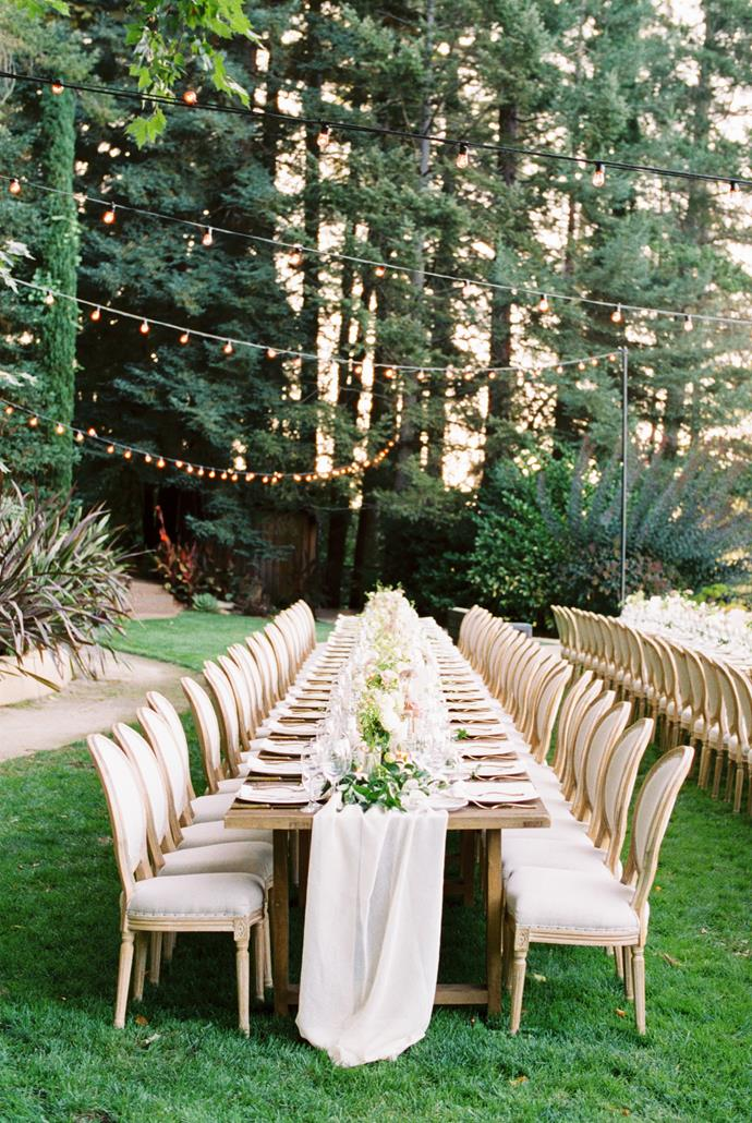 **On the style of the reception:** Through a hidden garden pathway, the guests entered the reception of long tables, subdued mauve and white wildflowers and flickering candles shadowed by cypress and pine trees overlooking an infinity pool and the blue hues over the valley as the sun set.