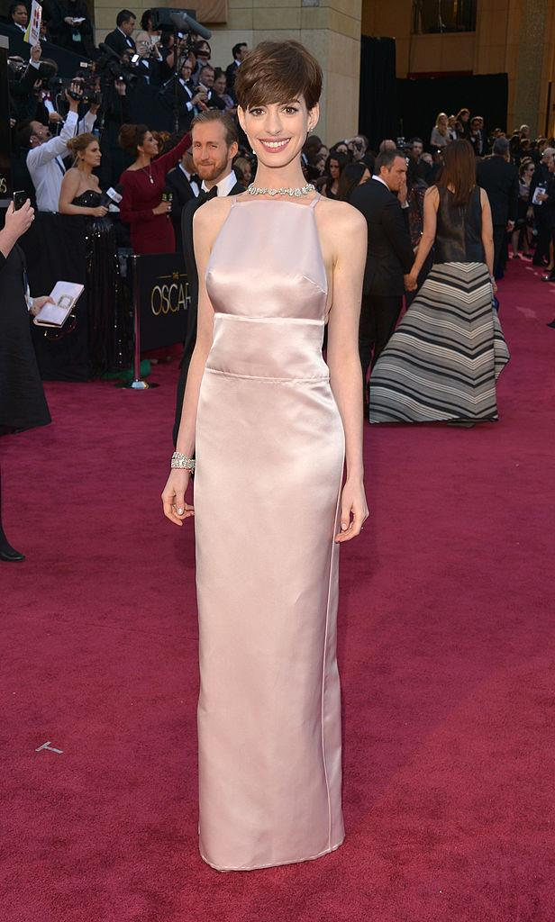 **Anne Hathaway in Prada at the 2013 Academy Awards** <br><br> If Gwyneth Paltrow wore the Oscars' most controversial pink dress, then the Prada dress that Hathaway wore to pick up her award for *Les Misérables* is a close second. But even if few could divert their attention from the distracting stitching on the top half of the dress, there's no denying that the gown fit Hathaway like a glove.