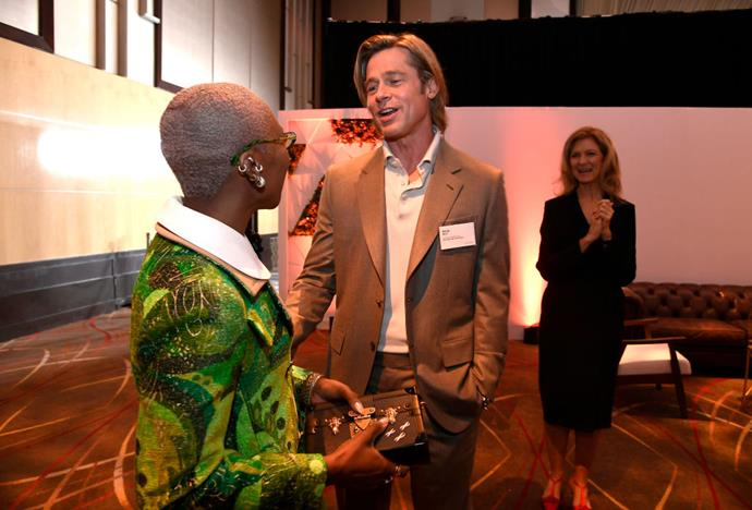 Brad Pitt (wearing a very unnecessary name tag) in conversation with Cynthia Erivo.