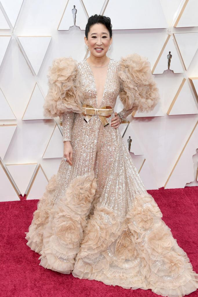 "**Sandra Oh in Elie Saab Haute Couture** <br><br> ""I hear you cynics, it is a lot of peachy ruffle and is indeed nearing the acceptable limits of nacreous sheen—and that bow is making me want Haigh's chocolate—but I'm giving Ms. Oh's Elie Saab high marks for at least having a fraction of the wearer's personality. She shines onscreen. And so should her dress."" *— Tom Lazarus, Copy Director*"