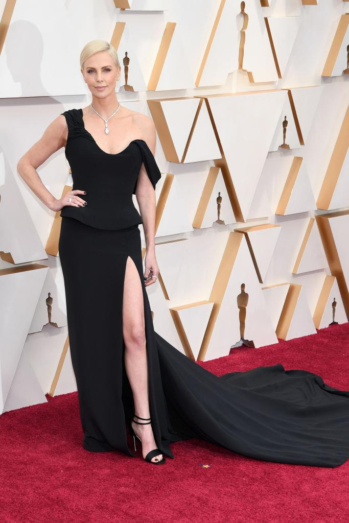 "**Charlize Theron in Christian Dior Haute Couture** <br><br> ""Charlize always makes it look so easy—and serves as a reminder that black really is the chicest shade on the red carpet. The fitted bodice and thigh-high split is both demure and sexy, which is a hard line to walk."" *— Brooke Le Poer Trench, Beauty and Wellness Director*"