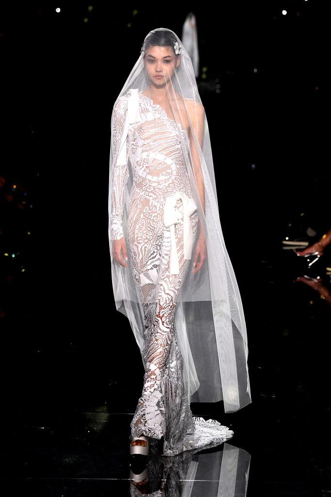 """**Tom Ford** <br><br> Up-and-comer Mika Schneider closing the show in this one-shoulder lace bridal gown was the perfect fashion moment, walking the line between classicism and the inherently risqué aesthetic Ford is often associated with (we're referencing *that* Gucci [exposed G-string](https://www.harpersbazaar.com.au/fashion/exposed-g-string-trend-18833 target=""""_blank"""") from 1997, of course). <br><br> *Image: Getty*"""