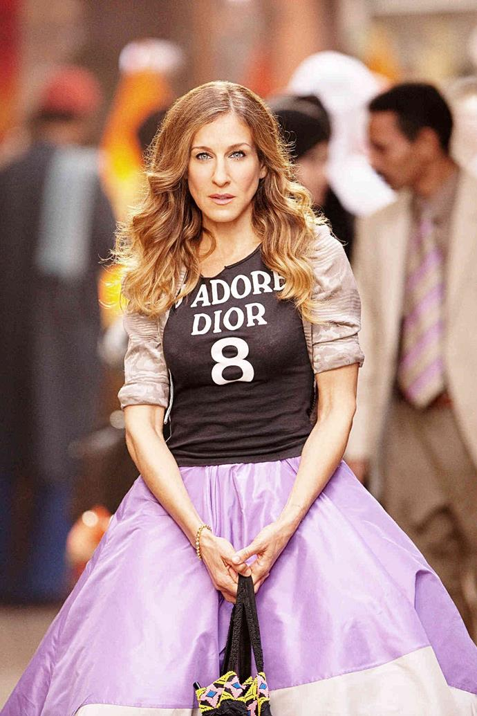 "***The Dior logo top*** <br><br> Another staple of John Galliano's time at Dior, Carrie sported one of the designer's famous 'J'adore Dior' tops in *SATC2* (over a decade after Lucy Liu famously wore a similar one when she [cameoed](https://www.harpersbazaar.com.au/culture/sex-and-the-city-cameos-19961|target=""_blank"") in season four). The style became a must-have wardrobe piece of the 2000s, many years before Balenciaga and Gucci's logo-adorned tees stole our attention."